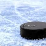 bigstock-black-hockey-puck-on-ice-rink-22755464-583x381